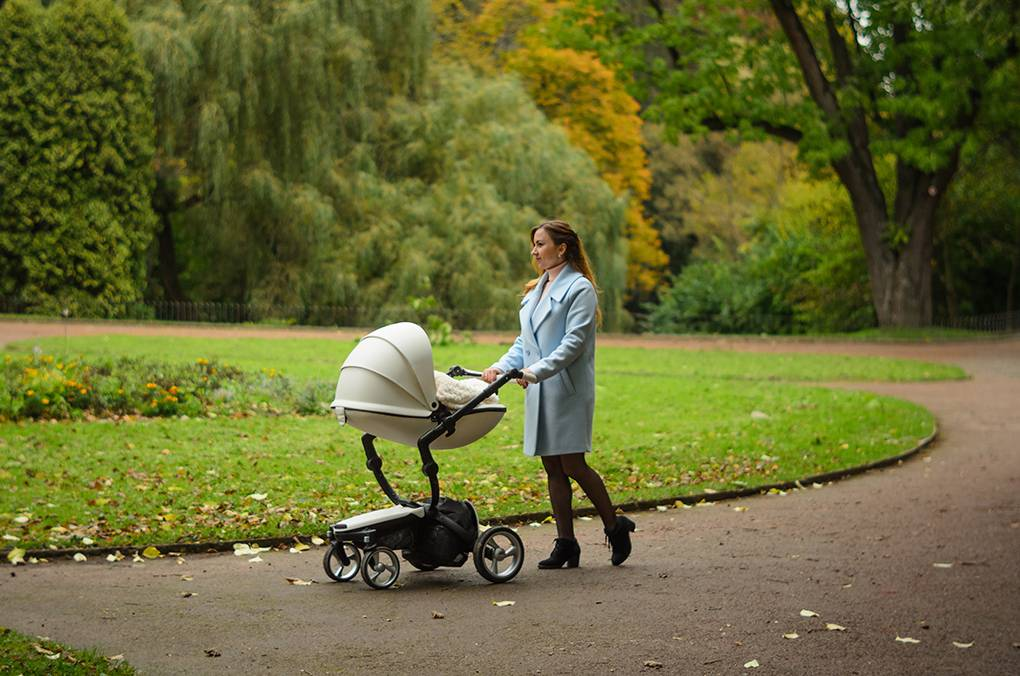 Family, child and motherhood concept - happy mother walking with baby stroller in park